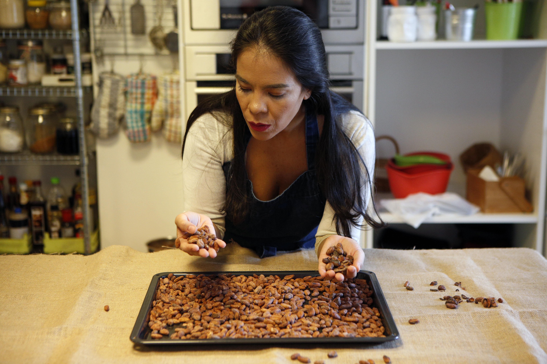 Helen seleccionando cacao de una bandeja antes de tostar