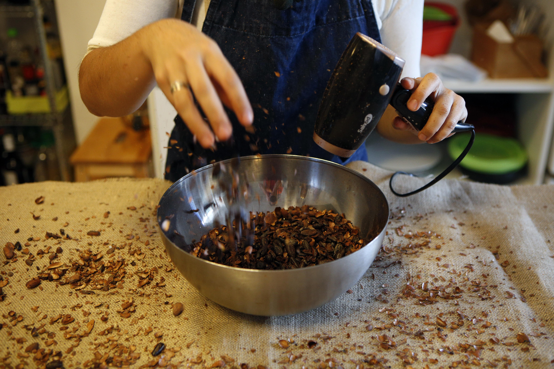 Separando el cacao tostado de la cascarilla con un secador de pelo en una cocina