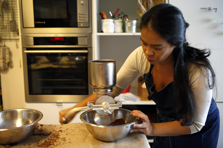Helen premoliendo cacao antes de llevarlo a la conchadora en un molino tradicional