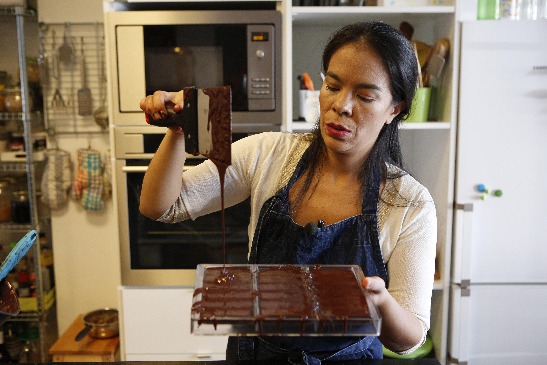 Mujer derramando chocolate en moldes de tabletas