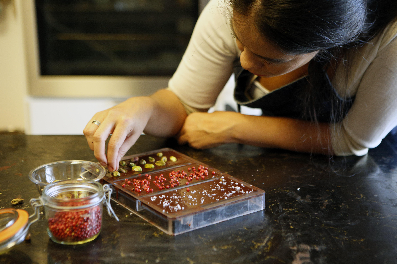 Mujer decorando tabletas de chocolate con pimineta rosa, cardamomo y sal